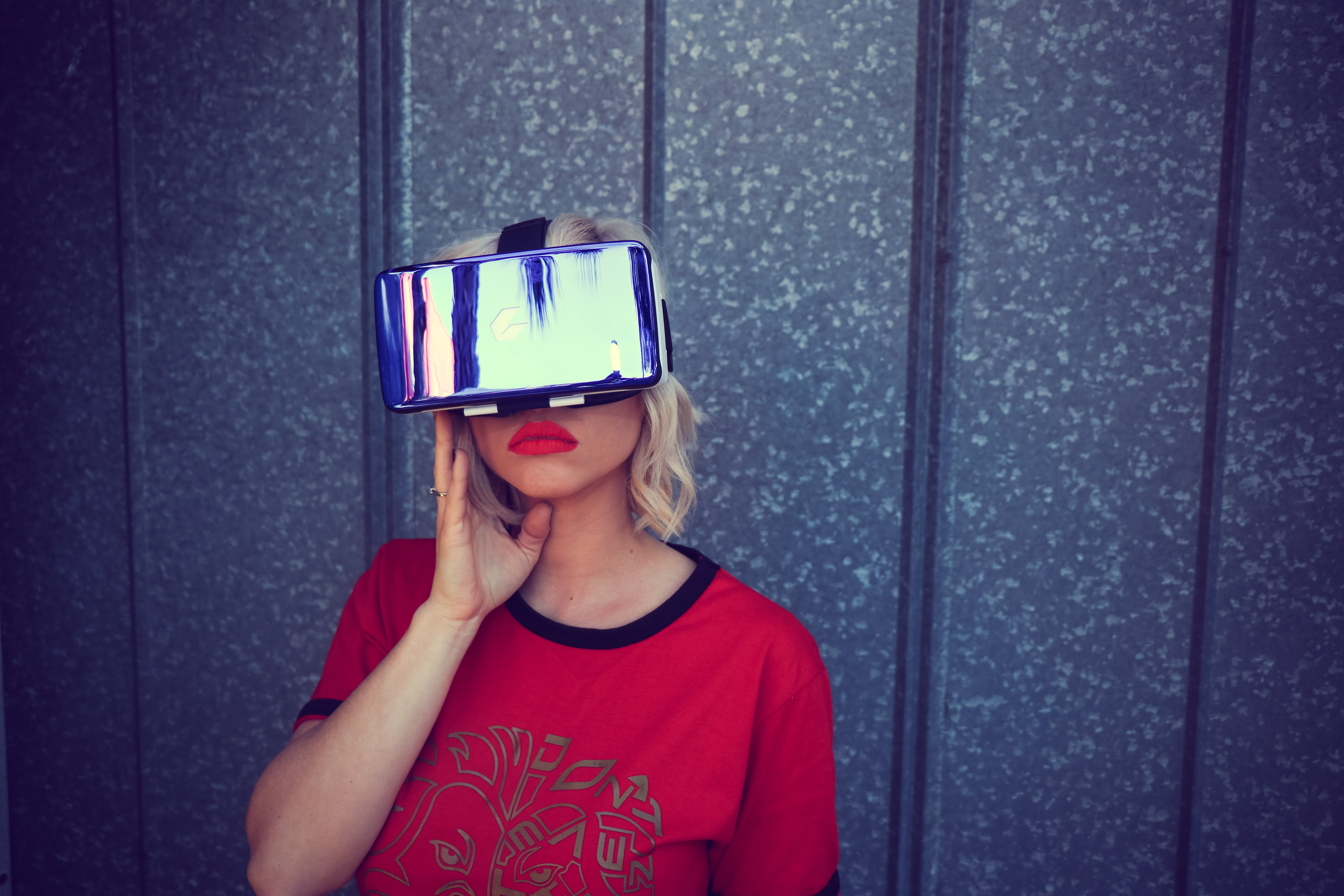 A girl with red sweater and lipstick are wearing a VR-headset and posing