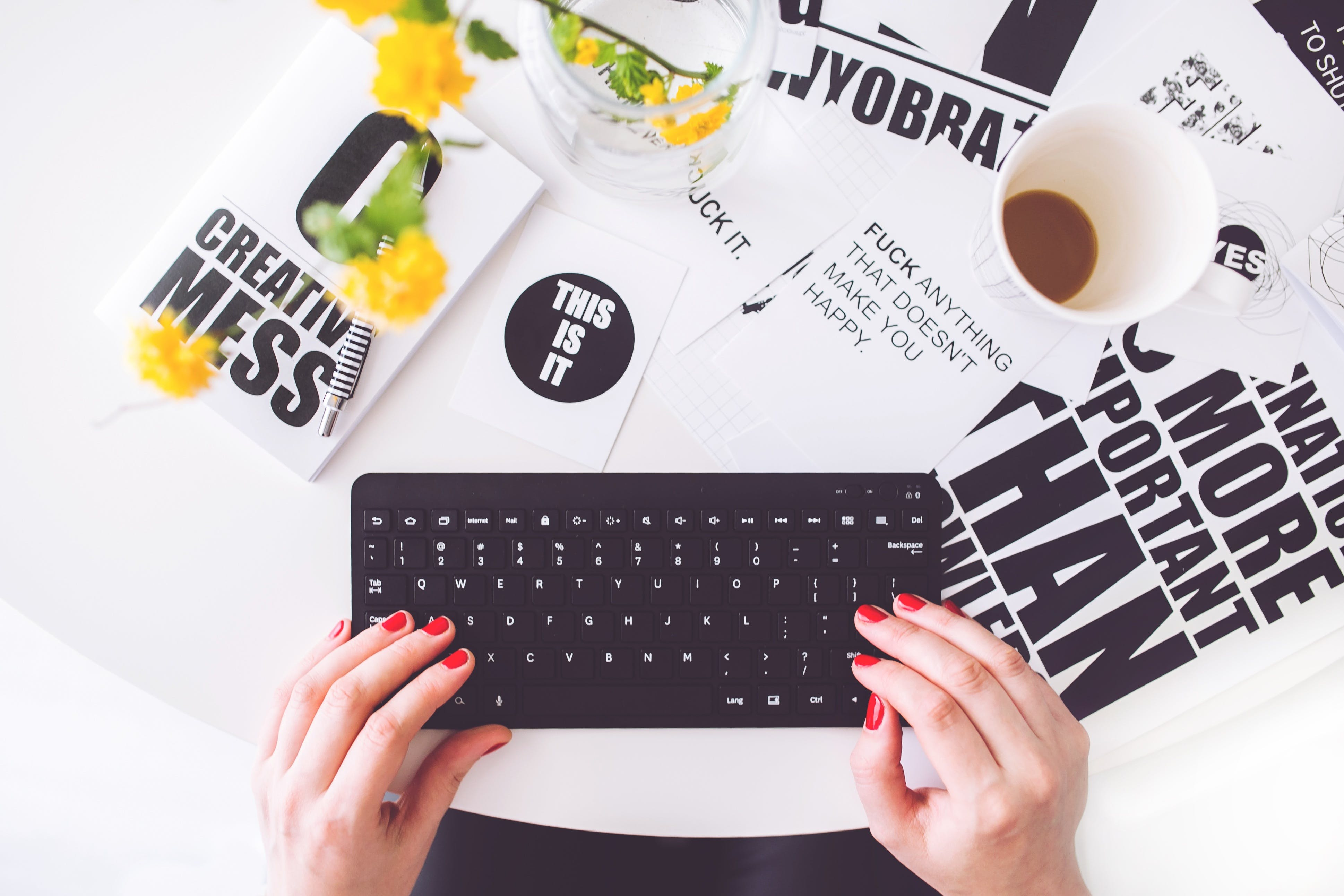 Girl with red nail polishing typing on a keyboard, on a table with a bunch of paper with quotes