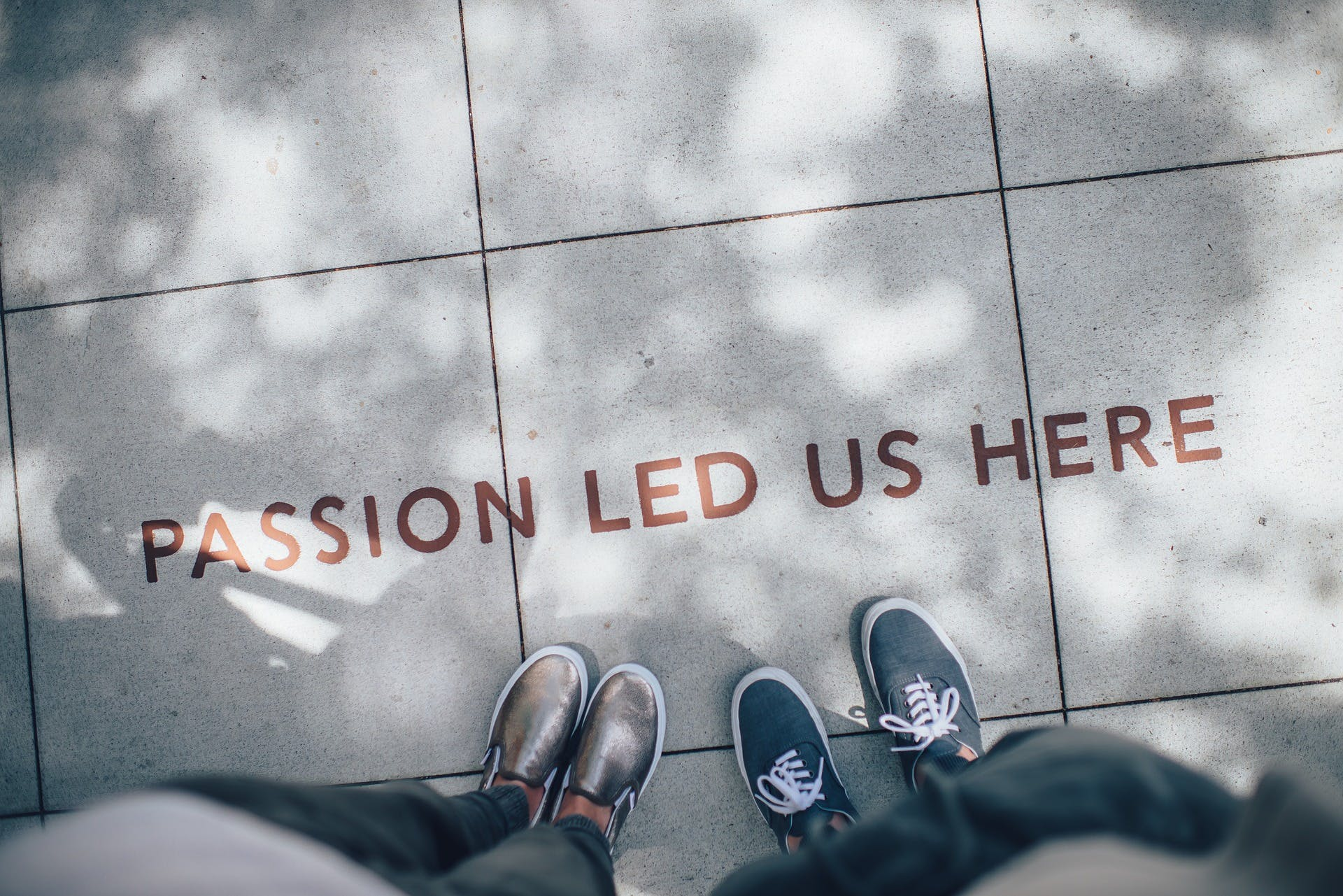 Two people standing on a road and in front of them there is a text on the road that says: 'Passion led us here'