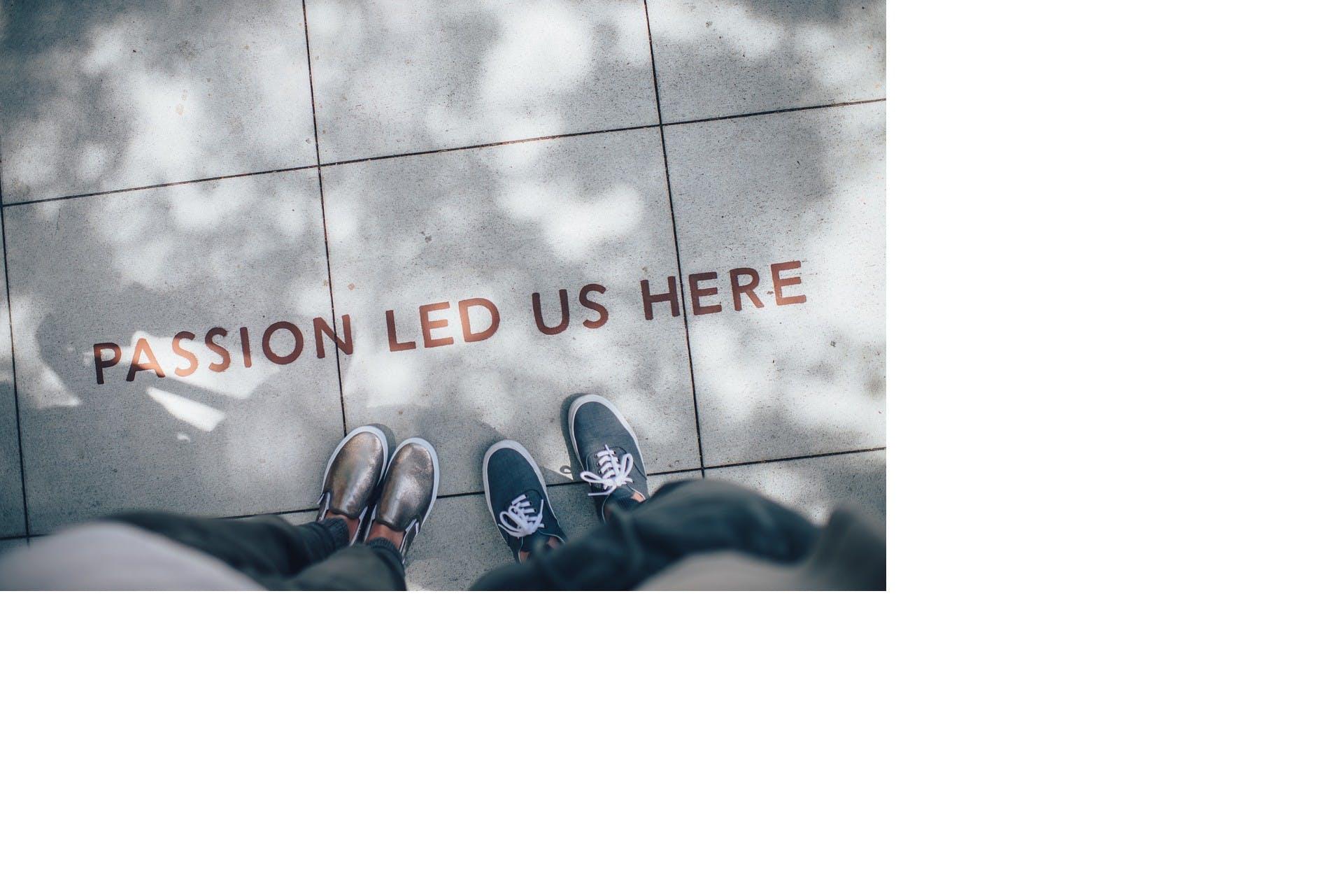 Två personer står på en väg och framför dem står det 'Passion led us here'