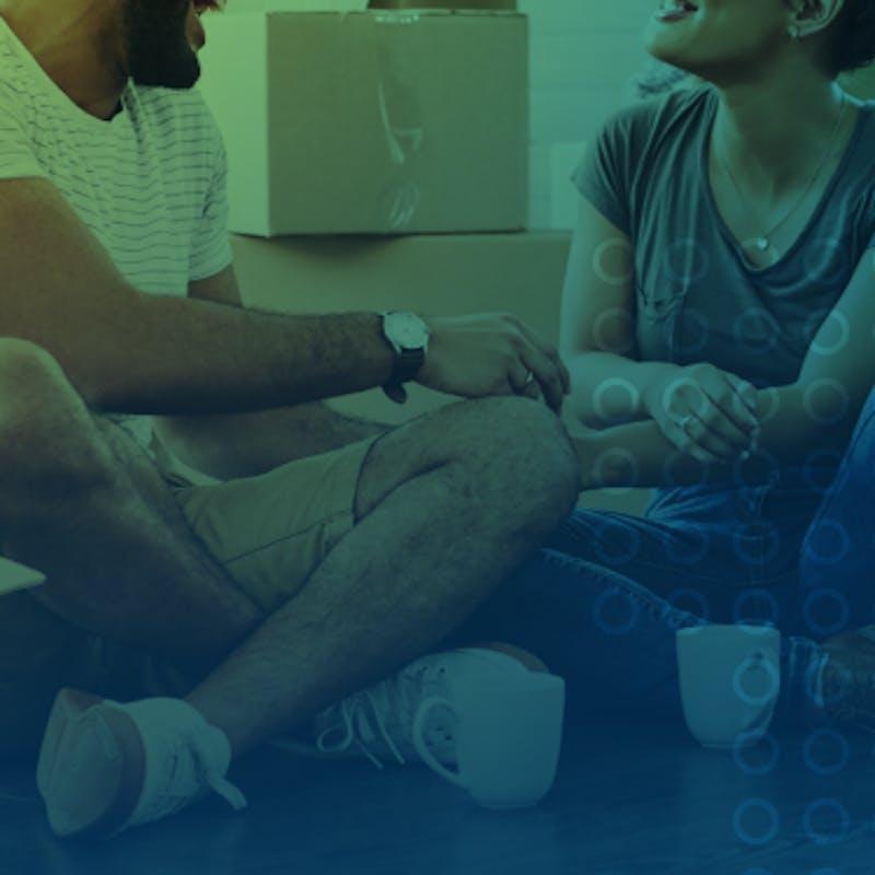 casal sorrindo sentados ao lado de caixas