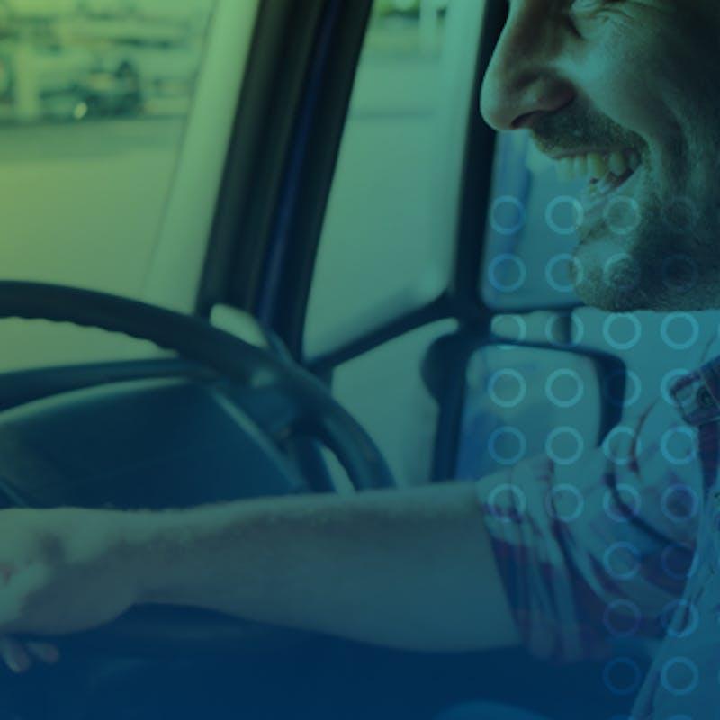 homem sorrindo enquanto dirige um caminhão