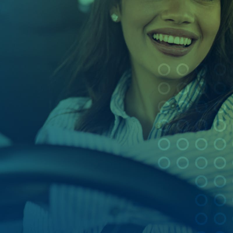 mulher branca sorrindo enquanto dirige