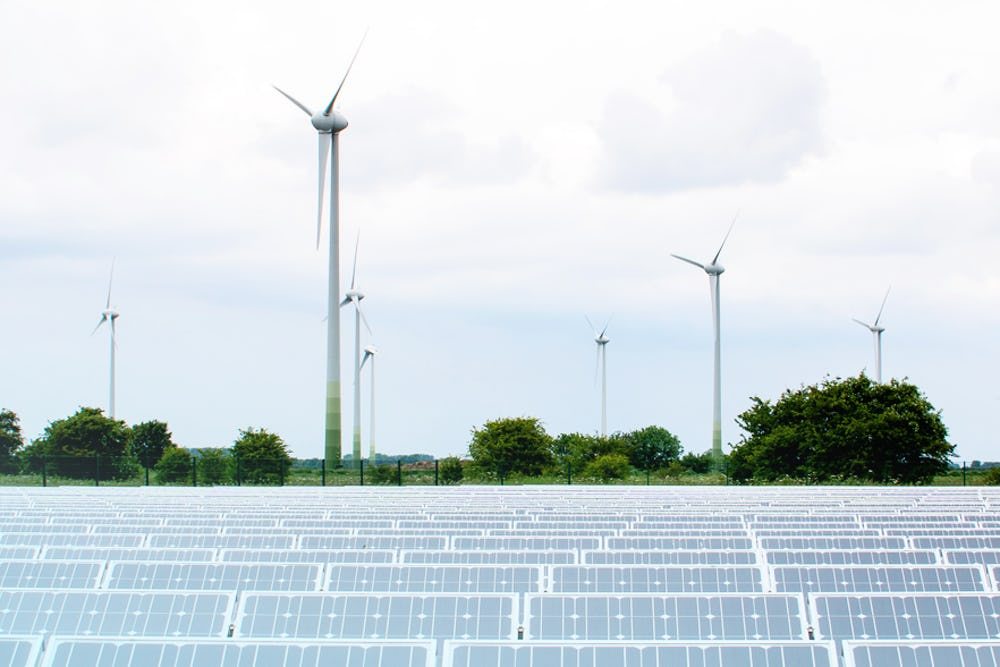 Image of solar panels in the foreground and an onshore wind farm in the background demonstrating that Skydiamonds are made using renewable energy