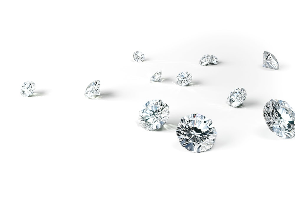 A scattering of 12 beautiful, radiant Skydiamonds on a white background - pure, ethical diamonds