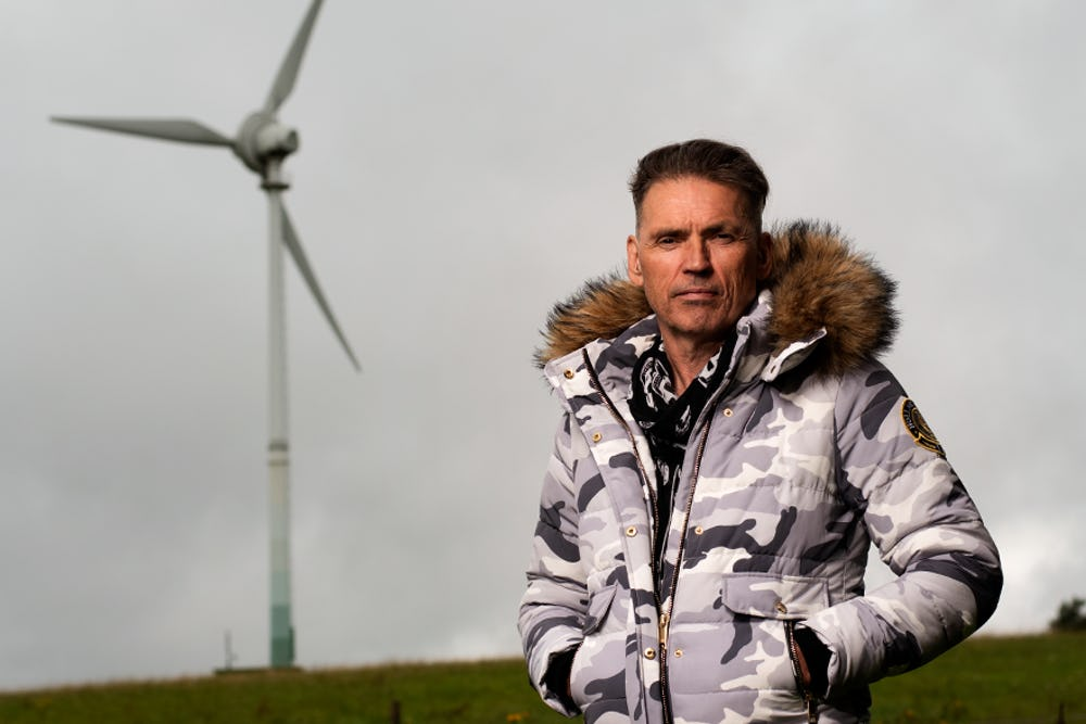 Dale Vince, founder of Skydiamond, with wind turbine in the background