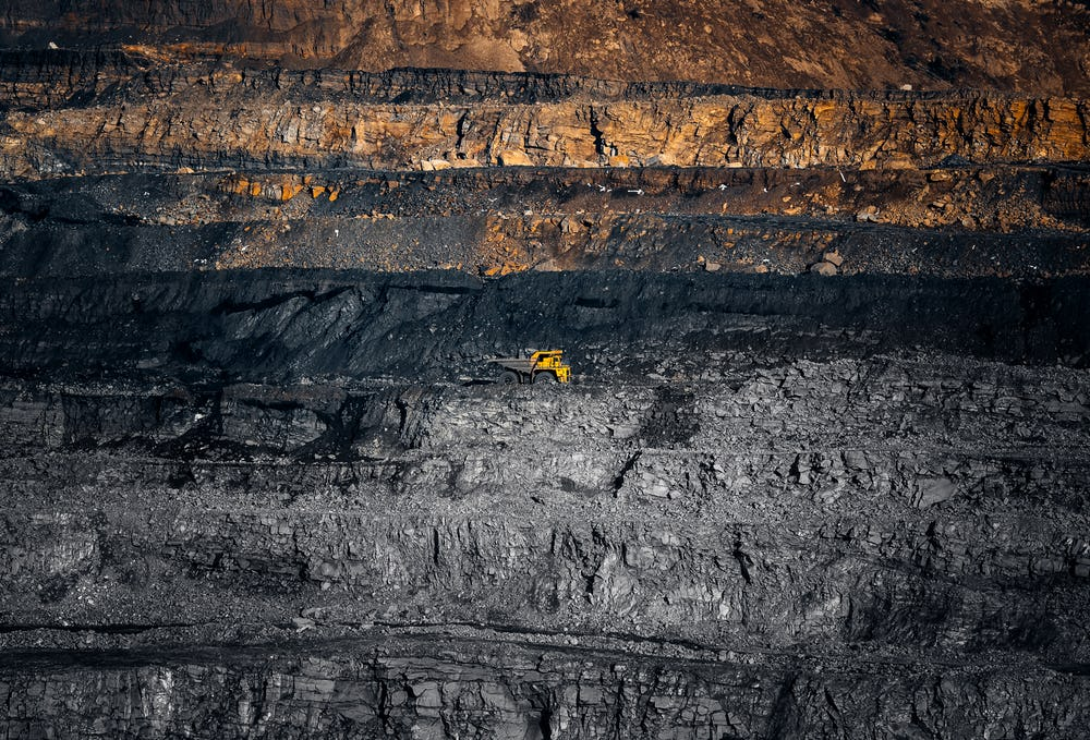 A giant hole created by a diamond mine dwarfs a yellow dump truck. Skydiamond's eco-friendly diamonds don't lead to environmental damage
