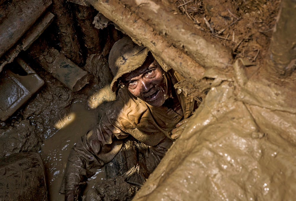 A miner looks up from a muddy hole where he's looking for diamonds. Skydiamonds are zero-exploitation products