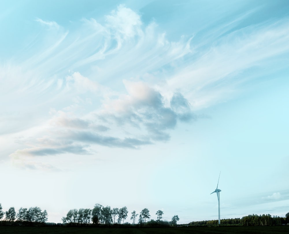 Clouds over a silhouetted landscape showing a wind-turbine