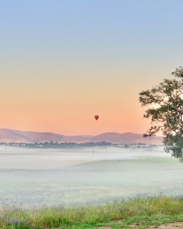 View from Gawthorn's Hut in Mudgee featuring a Balloon Aloft hot air balloon in the distance.
