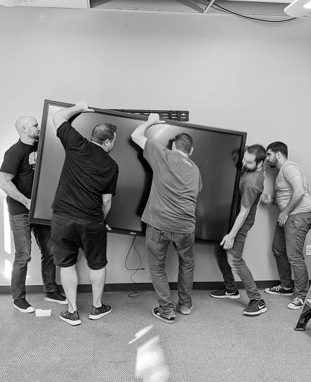 Some of the SoCreate Team are lifting a 300-pound touch conference room display.  This was one of many as we have them in every room at the SoCreate HQ.