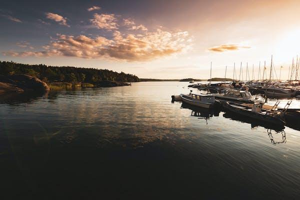 Veneet satamassa auringon laskiessa