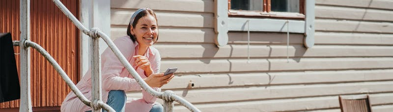 Nainen käyttää vertailupalvelua puhelimella