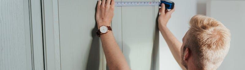 Mies mittaa keittiökaappeja remonttia varten