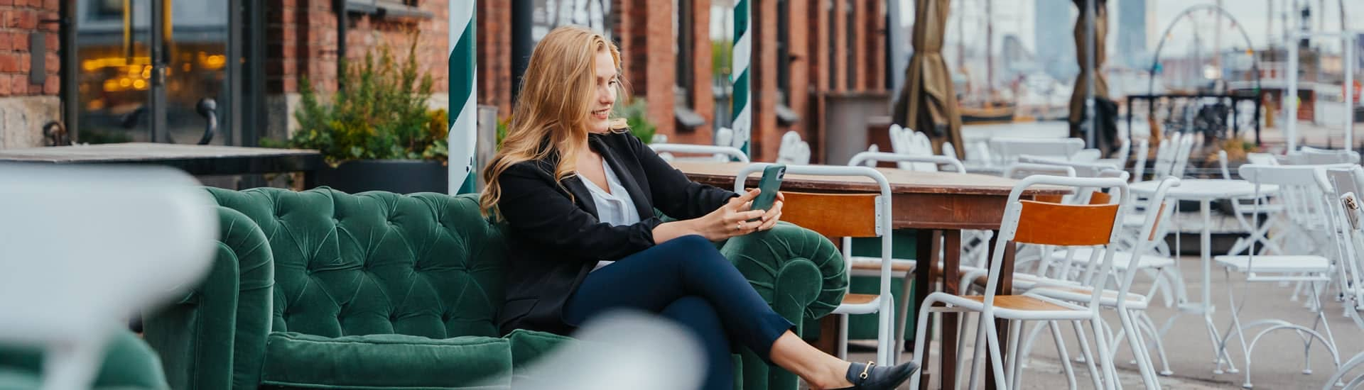 Nainen selaa puhelimella joukkorahoituspalveluita