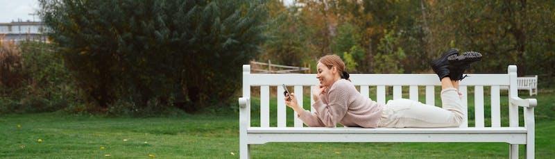 Nainen viettää aikaa puistossa ja vertailee lainoja