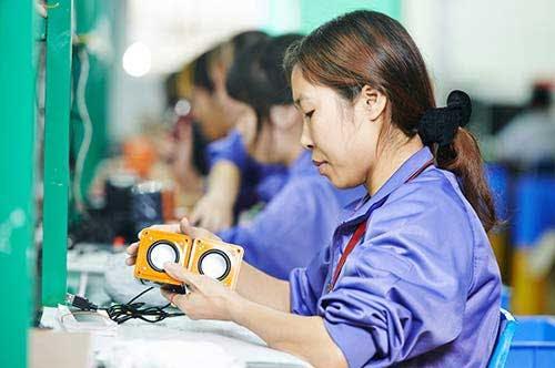 Factory worker assembling speakers