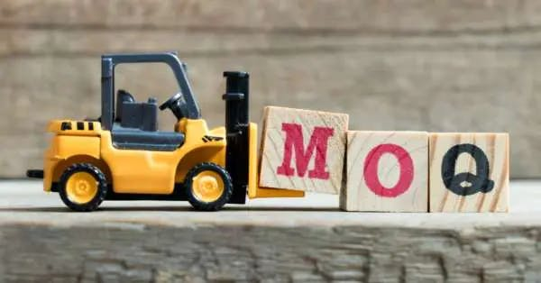 Image of a toy truck in front of wooden blocks spelling MOQ
