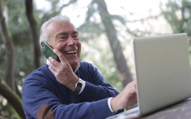 Man using phone and laptop