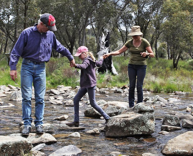 Family of three walking in a creek