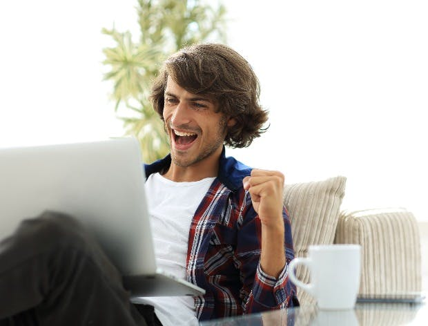 Happy young man looking at laptop