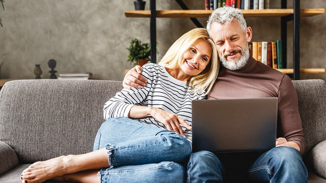 Man and Woman sitting on couch looking at computer