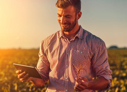 Man standing in a field with a tablet
