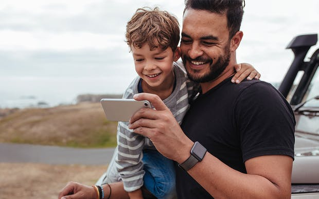 Man holding his son and looking at a mobile phone