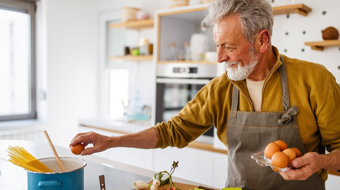 Older man cooking in kitchen