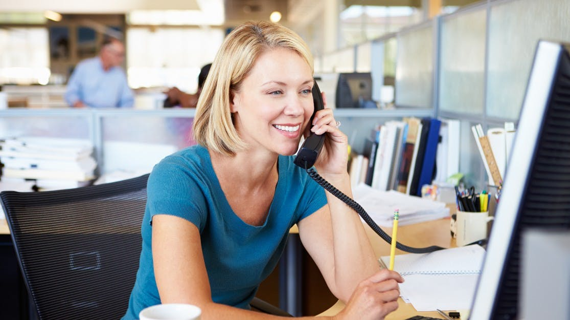 Lady using desk phone in office