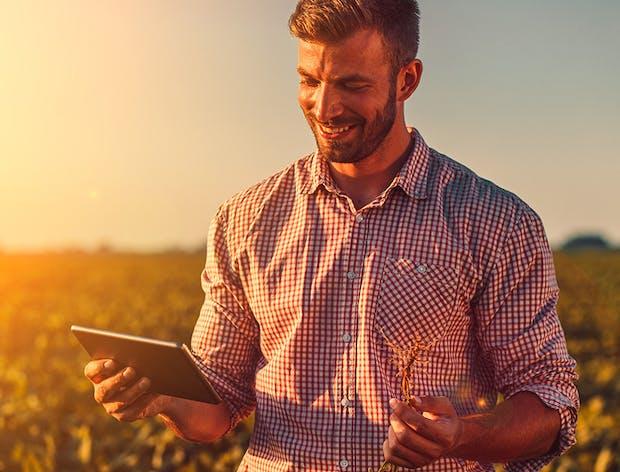 Man looking at tablet in field
