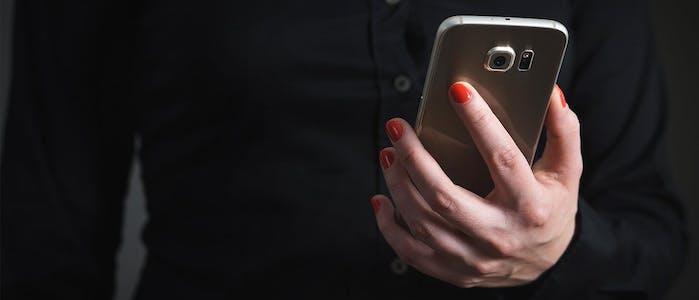 Frau hält Handy in der linken Hand