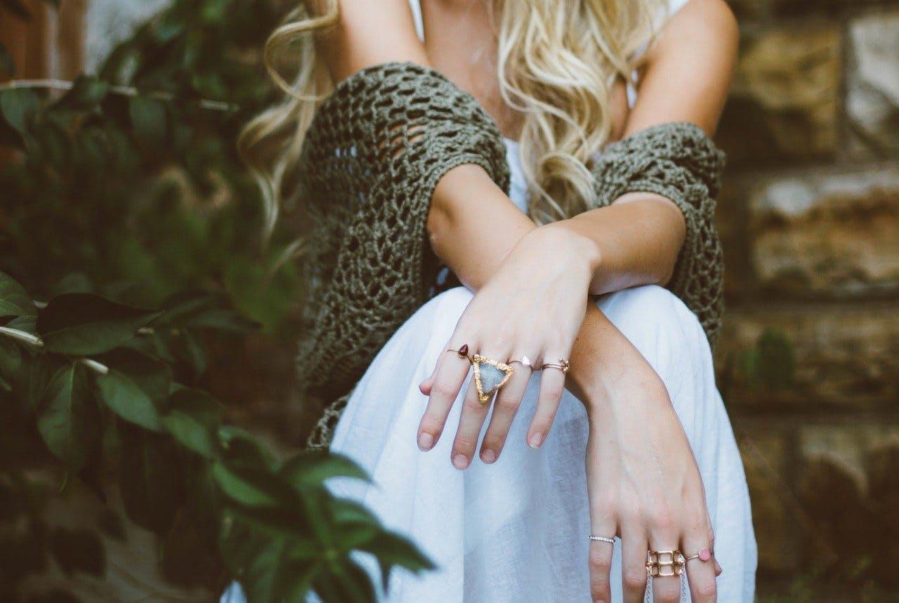 Frau in weißem Kleid mit Ringen an den Fingern