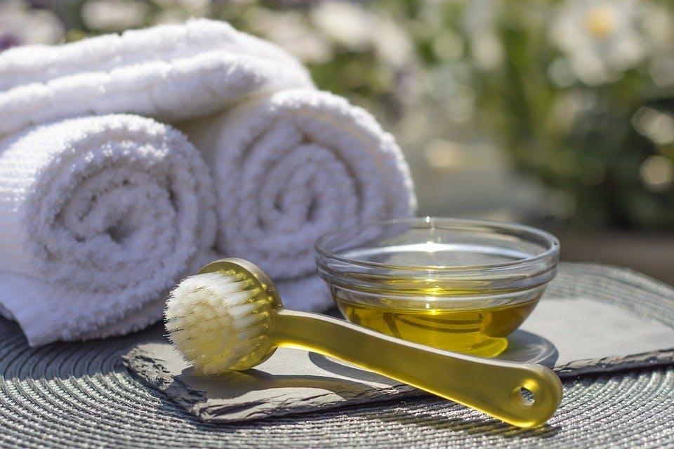 Massageöl in Schälchen neben Handtüchern und Bürste