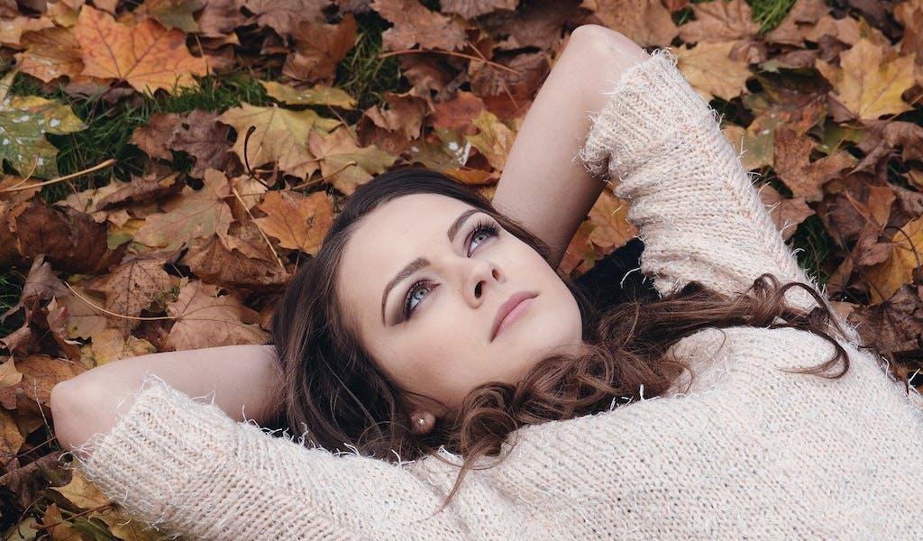 Frau liegt im Laub