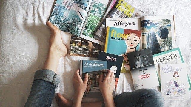 Bücher und Zeitschriften auf einem Bett verteilt