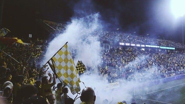 Fußball-Fans jubeln im Stadion.