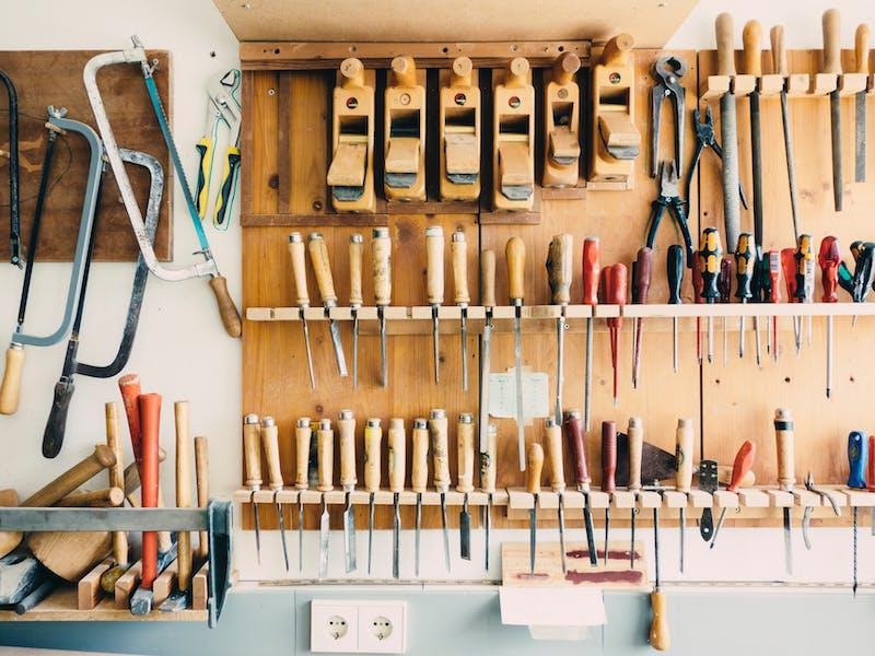 Holzwerkzeuge wie Hobel und Sägen an Wandregal