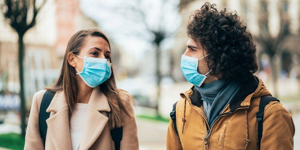 Ein Paar trägt jeweils eine blaue klinische Maske