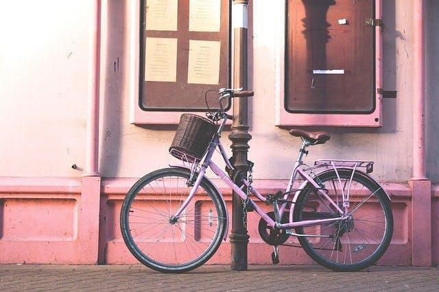 Rosa Fahrrad vor rosa Hauswand