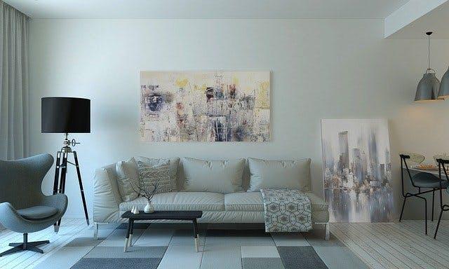 Stilvolles Wohnzimmer mit Bildern, weißem Sofa und einer eleganten Stehlampe