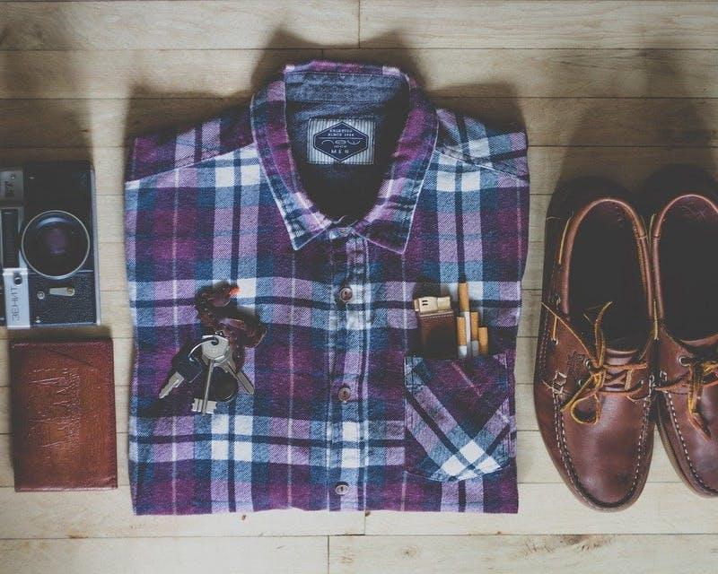 Gefaltetes Hemd, Schuhe und Accessoires auf Tischplatte