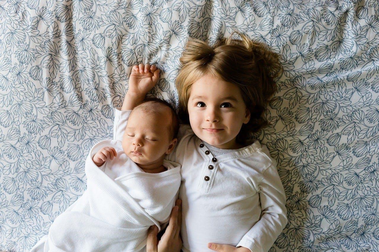 Baby und Kleindking liegen auf dem Rücken Seite an Seite