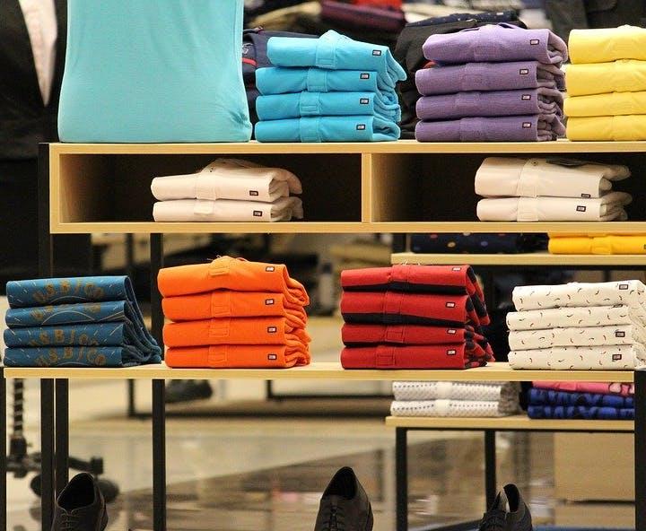 Gestapelte Hemden in verschiedenen Farben auf Verkaufstisch