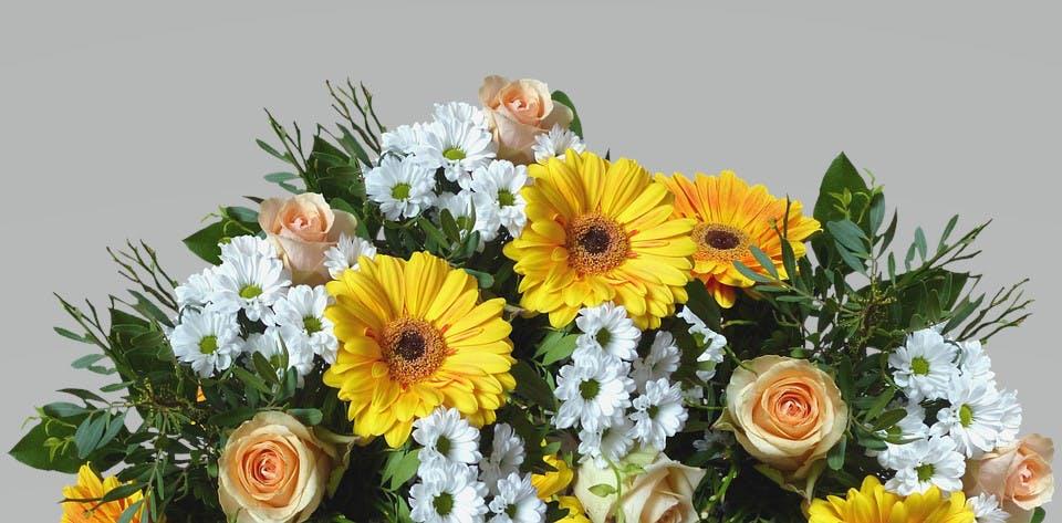 Blumenstrauß mit Blättergrün, gelben und weißen Blumen und gelben Rosen