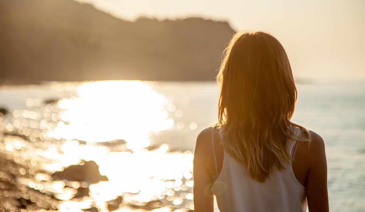 Frau steht mit Rücken zur Kamera am Strand