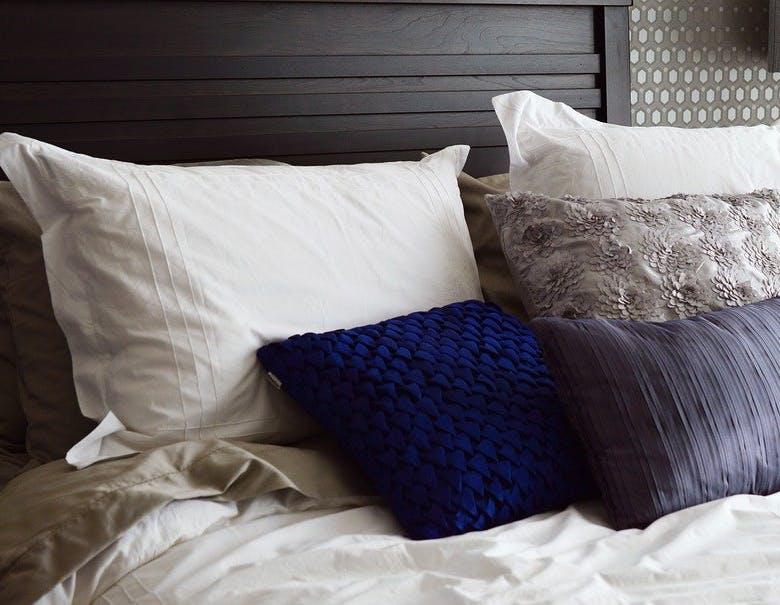 Bett mit Kopfkissen und Bettwäsche