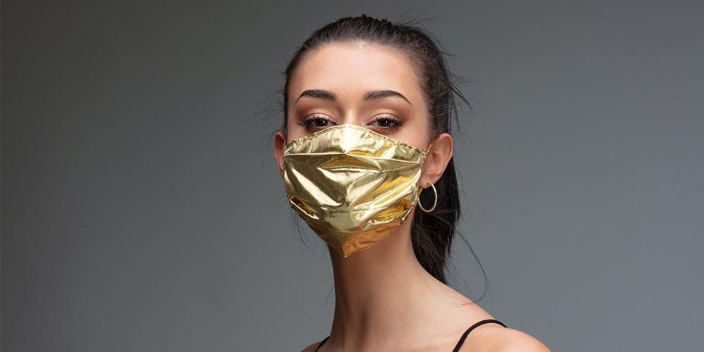 Eine dunkelhaarige Frau trägt eine goldene Maske