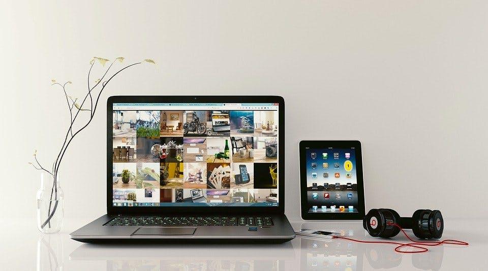 Laptop, Tablet und Kopfhörer mit MP3-Player auf heller Tischoberfläche