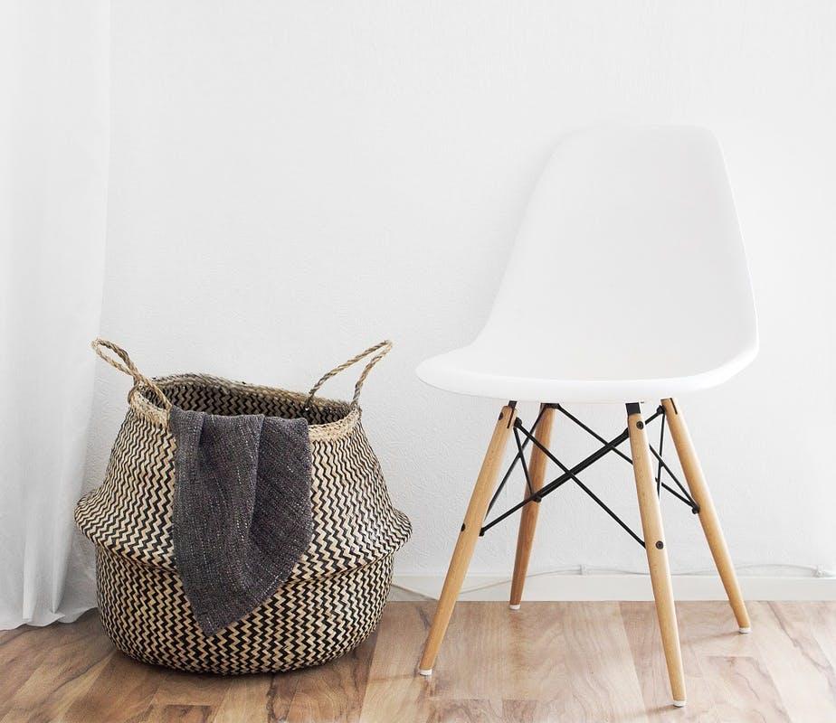 Design-Schalenstuhl und geflochtener Wäschekorb